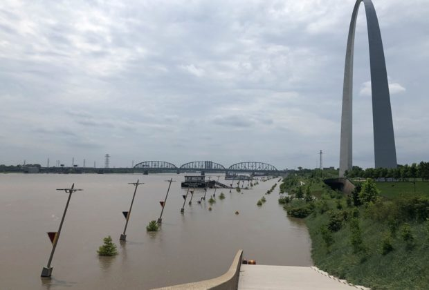 Floodwaters rise the hill below Gateway Arch National Park in St. Louis, MO.